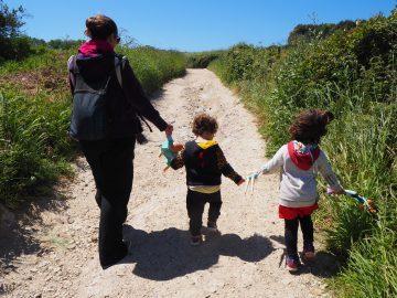 Mujer con dos niños paseando en un camino de tierra en Suiza