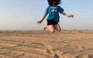 Niña saltando en Sudáfrica con camiseta de Viajes Beagle