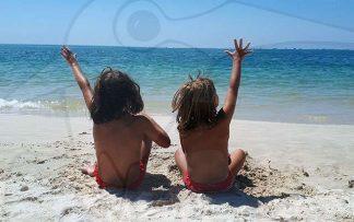 Niñas de espalda en la playa frente al mar
