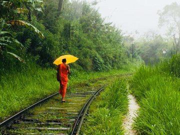 Monje budista paseando por los rieles del tren con paraguas en Sri Lanka